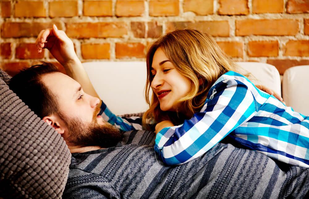 Elternsein Paar kuschelnd auf dem Sofa
