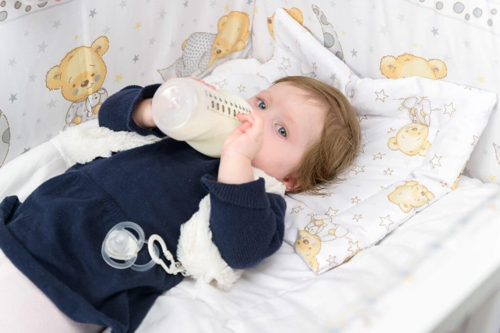 Baby trinkt Milch in ihrem Bett liegend