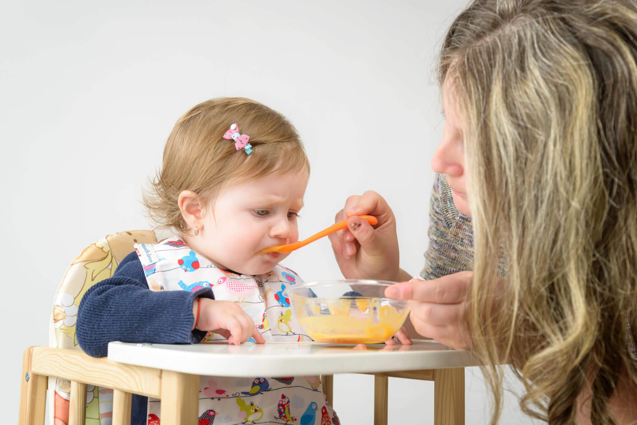Mutter füttert Tochter mit Brei, Kind sitzt in einem Kleinkinderstuhl mit Essensplatte