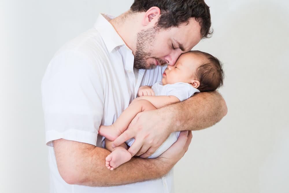 Vater trägt kuschelnd sein Baby auf dem Arm