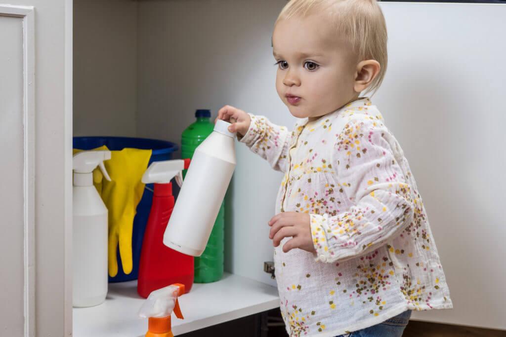 Kleinkind hat eine Flasche mit giftigem Haushaltsreiniger in der Hand