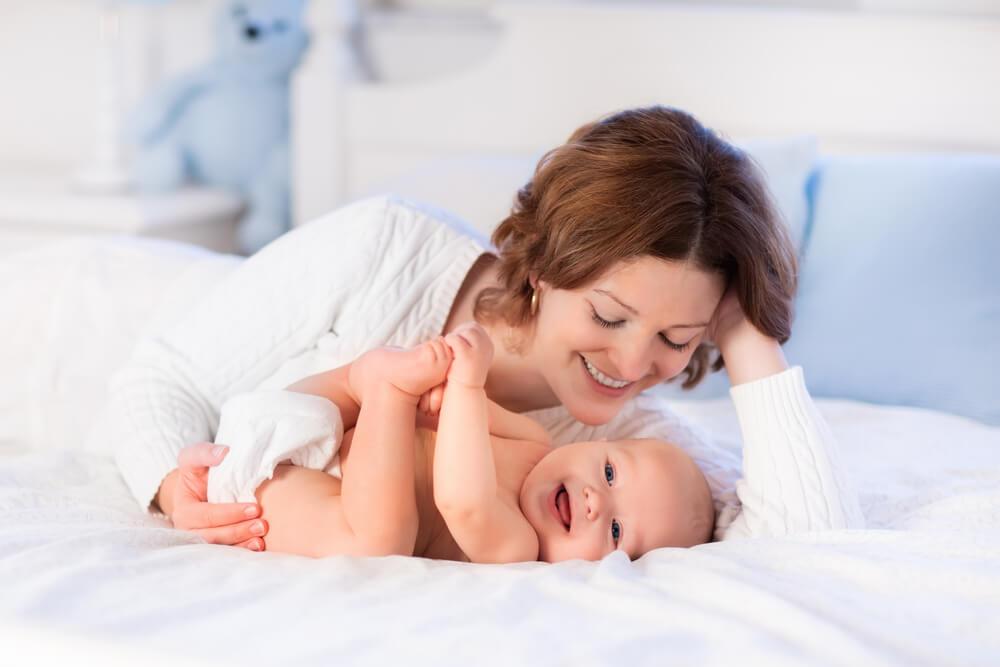Elternsein Mutter kuschelt mit ihrem Baby auf dem Bett