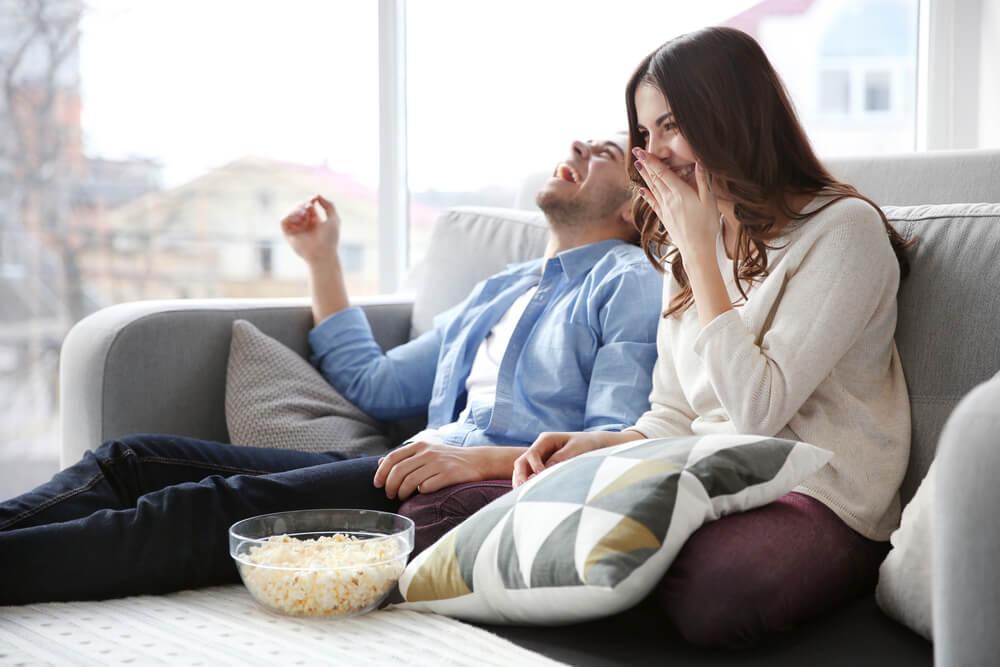 Elternsein Ein Paar sitzt mit Cornflakes lachend auf einem Sofa