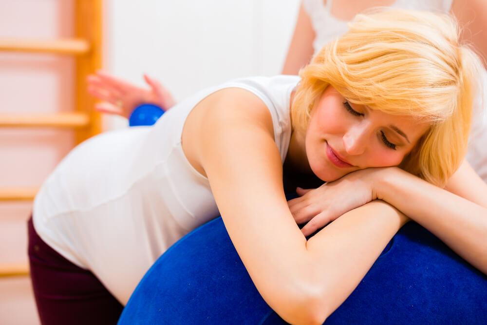 Werdende Mutter entspannt vor der Geburt liegend auf einem großen Gummiball