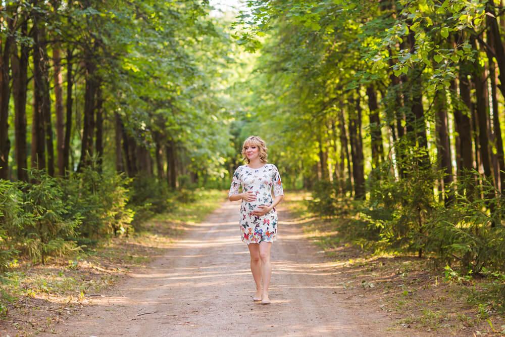 Schwangere geht in einem Wald spazieren