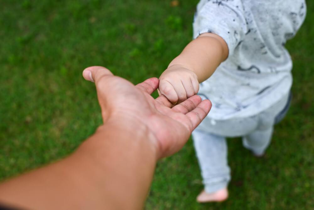 Baby lernt laufen an der Hand seiner Mutter