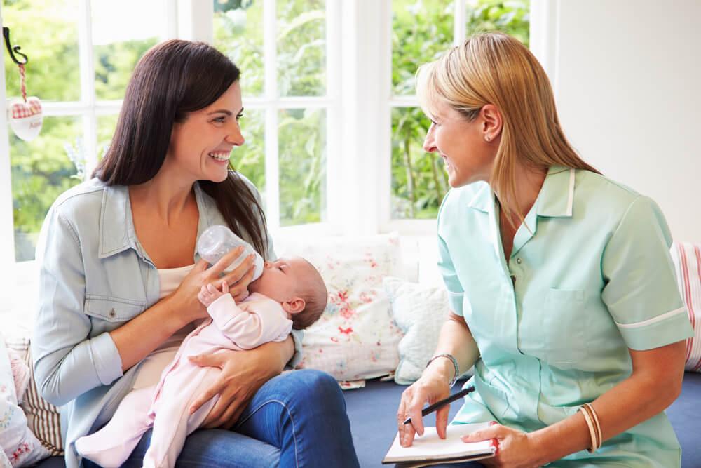 Hebamme berät eine Mutter, die ihrem Baby die Flasche gibt