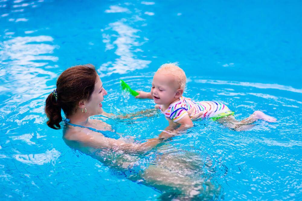 Mutter spielt mit Baby in einem Swimmingpool