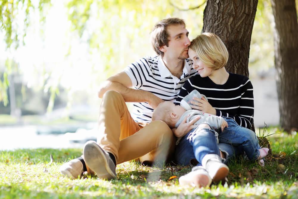 Eltern mit Baby in einem Park. Mutter stillt das Baby mit einer Flasche