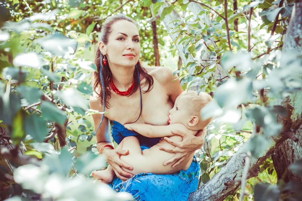 Frau stillt versteckt hinter Büschen ihr Baby