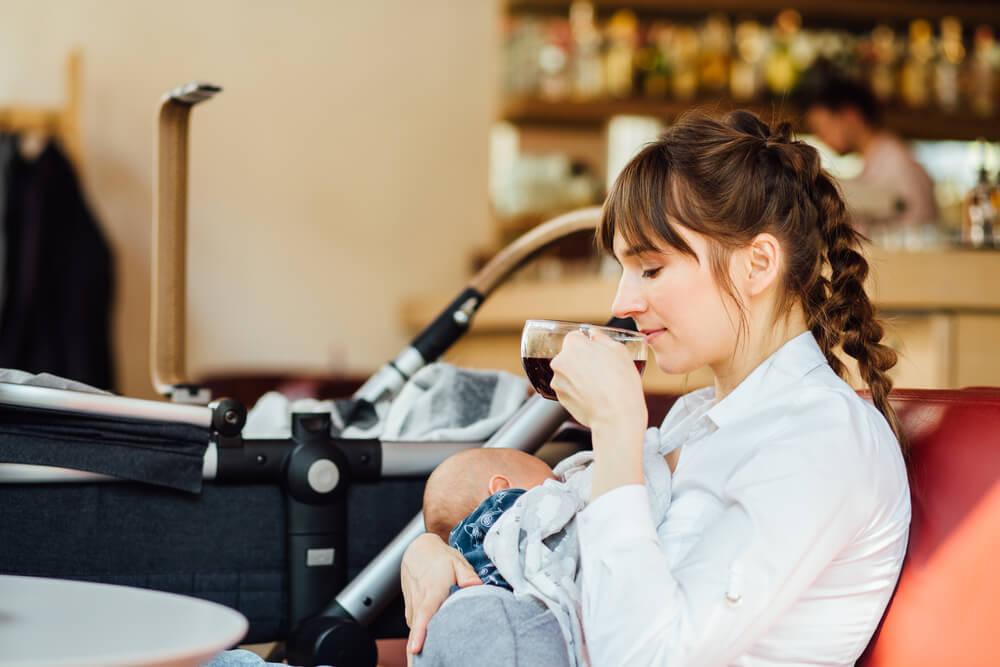 Stillen in der Öffentlichkeit Mutter sitzt stillend in einem Café