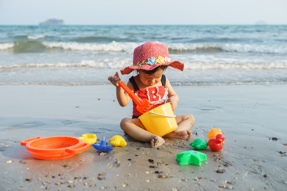 Baby sitzt mit Spielzeug am Strand