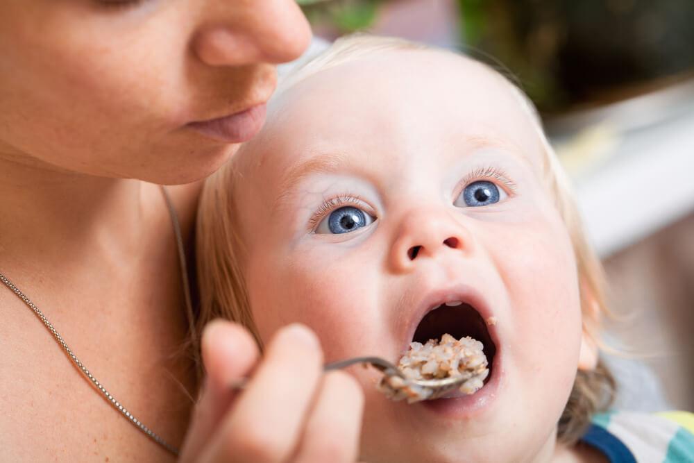 Mutter füttert Kleinkind mit Brei