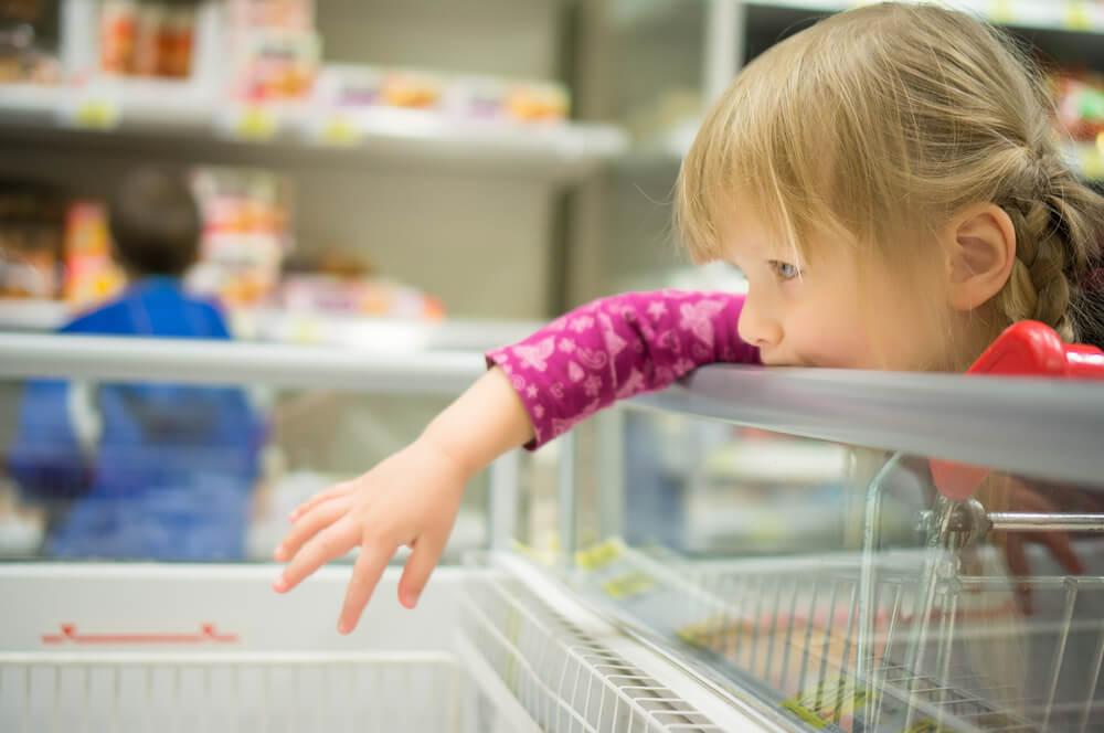 Kind greif beim Einkaufen in die Eistruhe