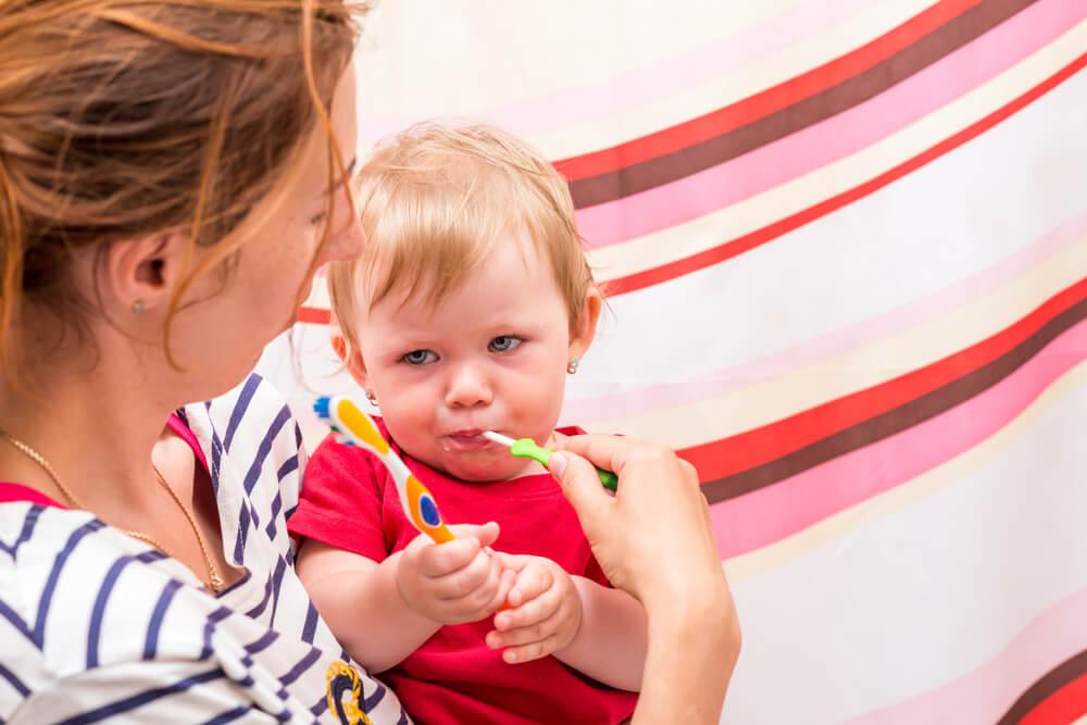 Mutter putzt Kleinkind die Zähne