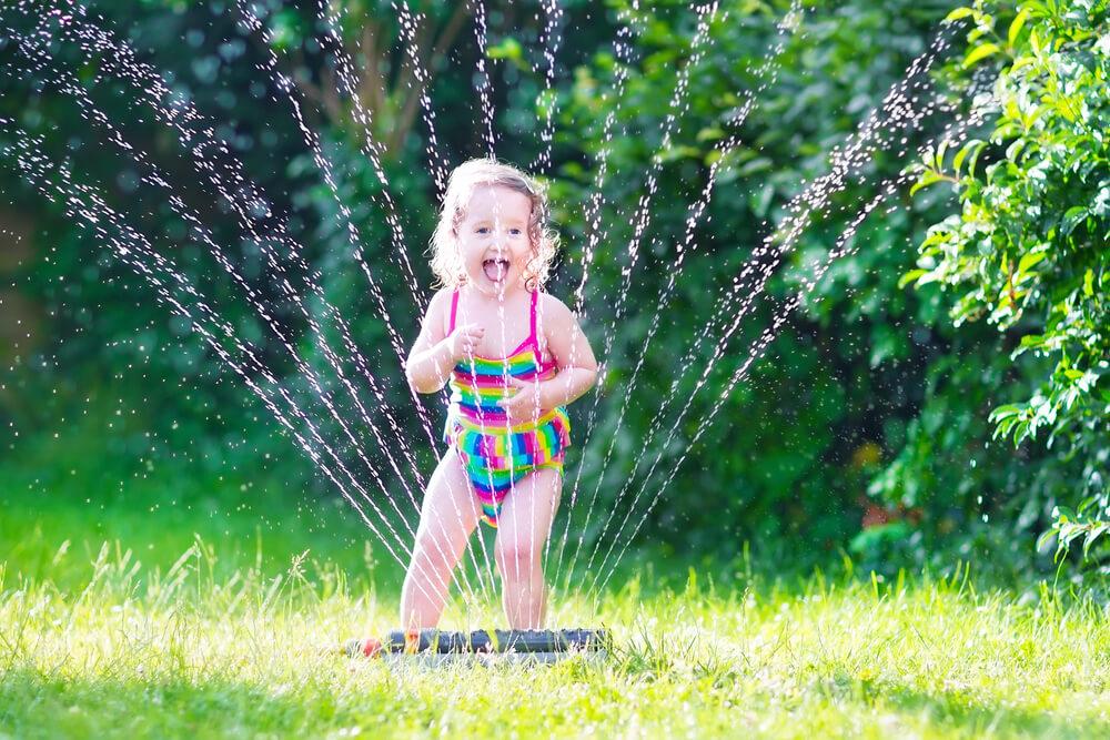 Tipps für heiße Sommertage: Kind unter einem Wassersprenger