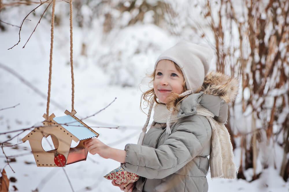 Jahreskreis - ein Kind legt Vogelfutter in ein Vogelhäuschen